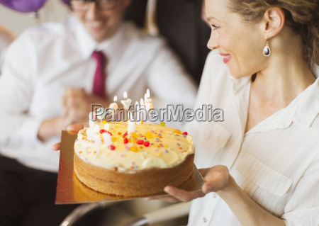 smiling businesswoman holding birthday cake with