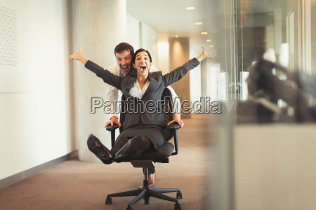 playful businessman pushing exuberant businesswoman down