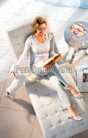 woman stroking dog while reading