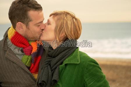 couple kissing on a beach autumn