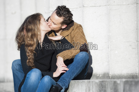 romantic couple kissing whilst sitting on