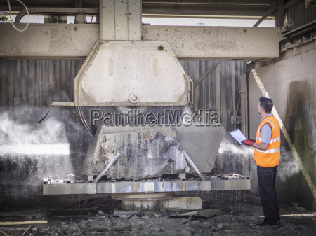 quarry worker inspecting stone saw
