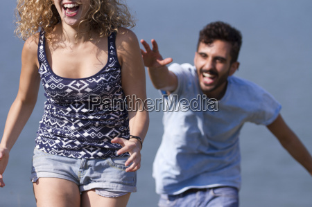 young man chasing woman laughing
