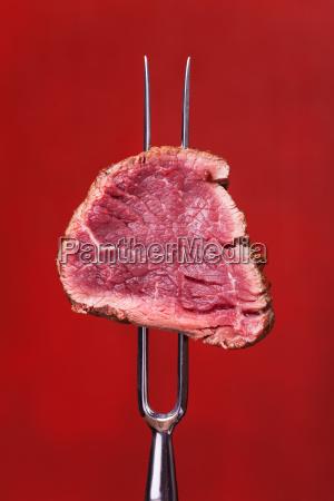 stueck steak auf einer fleischgabel