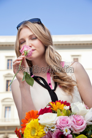 young woman smelling rose from bouquet