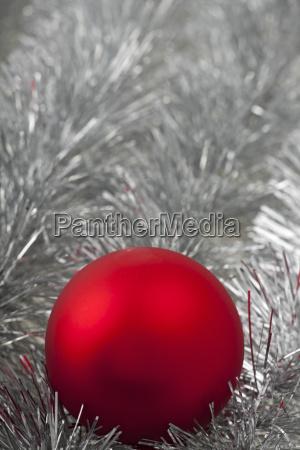 rote weihnachtskugel auf silberflitter