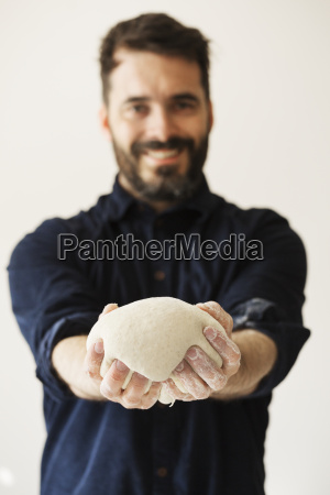 baker holding a portion of bread