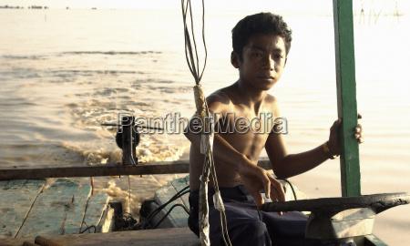 boy sitting on boat deck
