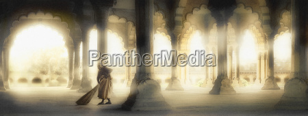 woman sweeping inside building of columns