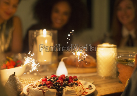 sparklers on berry pavlova dessert on