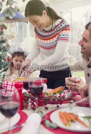 woman cutting turkey at christmas table