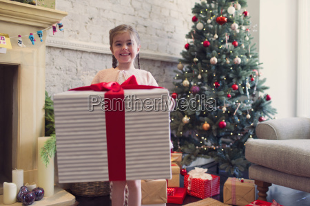 portrait enthusiastic girl holding large christmas