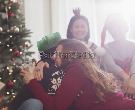 grateful girlfriend with christmas gift hugging