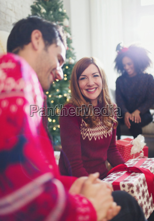portrait smiling woman opening christmas gifts
