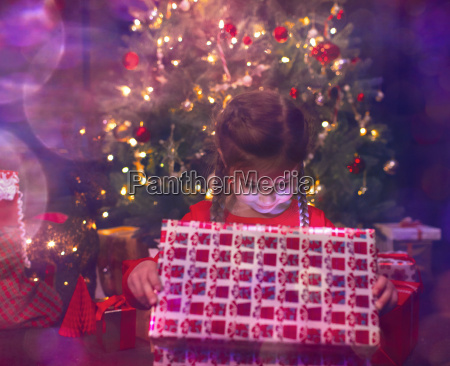 girl opening illuminated christmas gift