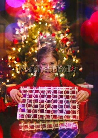 portrait smiling girl opening christmas gift