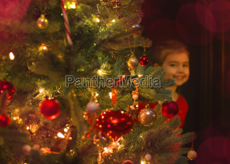 portrait smiling girl hiding behind christmas