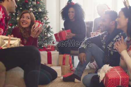 friends watching playful woman shaking christmas