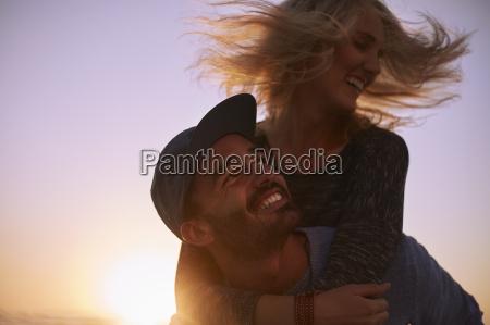 playful couple piggybacking