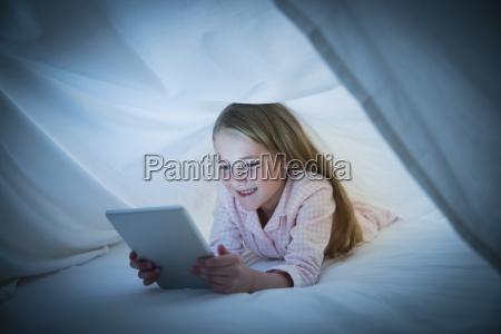 smiling girl using digital tablet under
