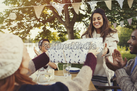 woman receiving birthday gift at garden