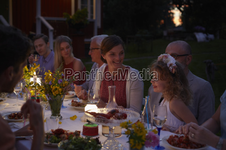 family enjoying candlelight patio dinner at