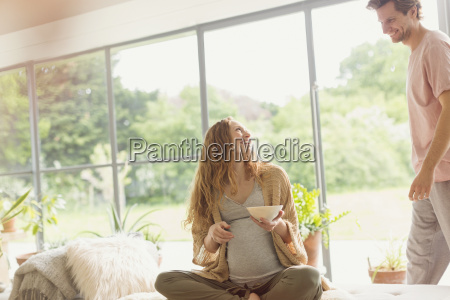 pregnant couple eating in living room