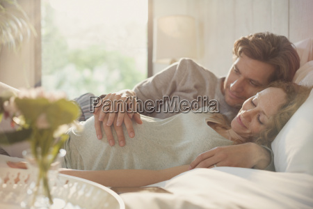 serene pregnant couple holding stomach on