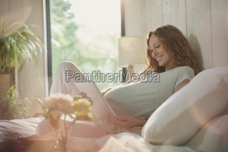 smiling pregnant woman using digital tablet