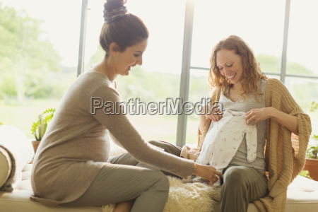 pregnant women looking at baby clothing