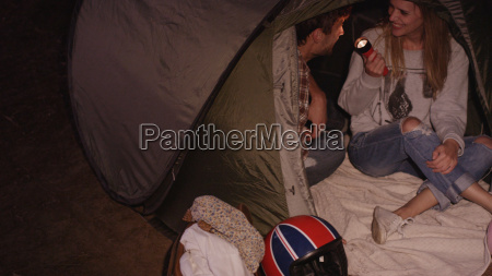young couple with flashlight inside camping