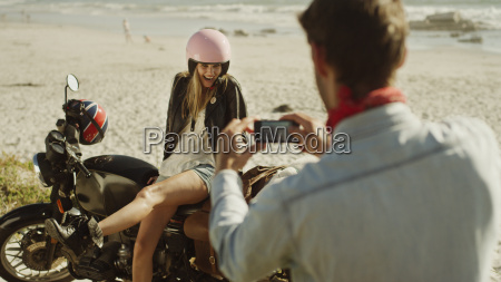 young man photographing woman on motorcycle