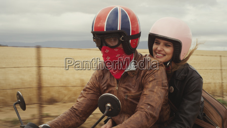 young couple riding motorcycle in rural