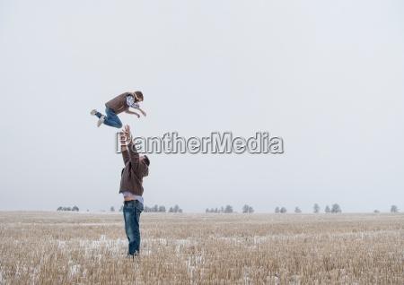 parent throwing child in air