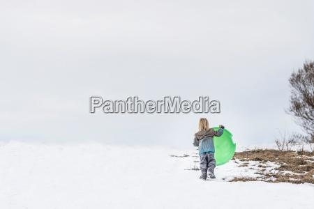 rear view of child carrying toboggan