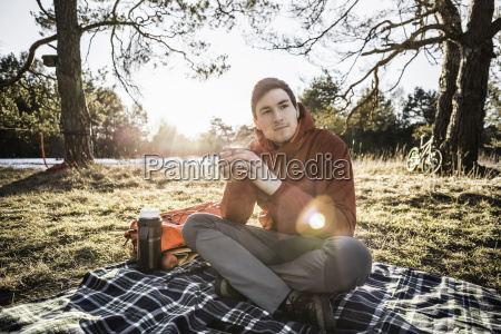 young man sitting on picnic blanket