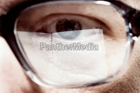 close up of mans eye reading
