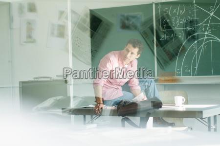 teacher sitting on desk in classroom