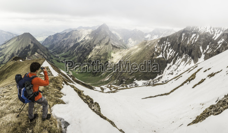 young male mountain trekker photographing valley