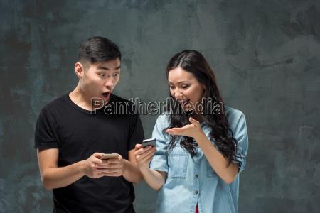 asian young couple using cellphone closeup
