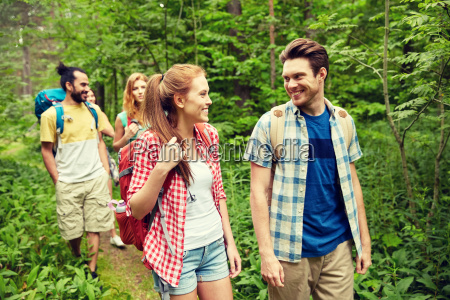 group of smiling friends with backpacks