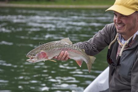 close up of fisherman holding rainbow
