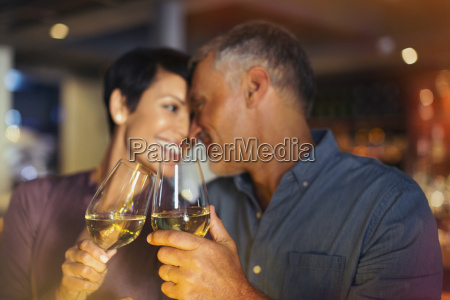affectionate couple toasting white wine glasses