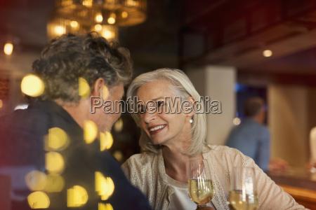 affectionate smiling senior couple drinking white