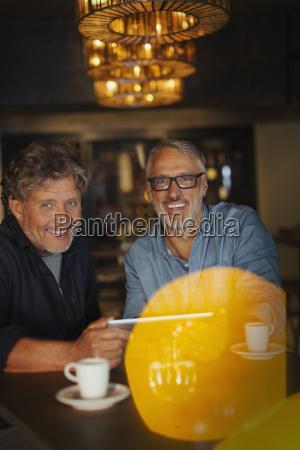 portrait smiling men using digital tablet