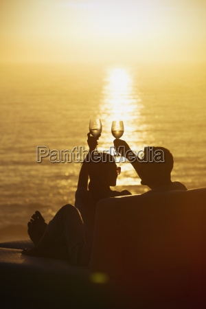 silhouette couple toasting wine glasses on