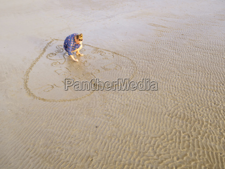 woman at the beach drawing heart