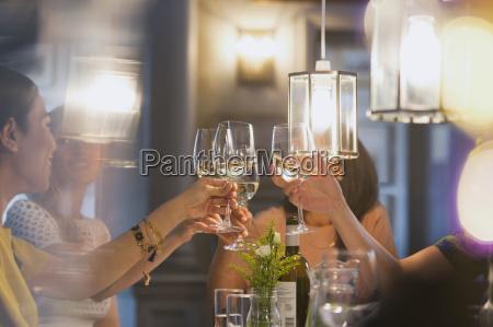 women friends toasting white wine glasses