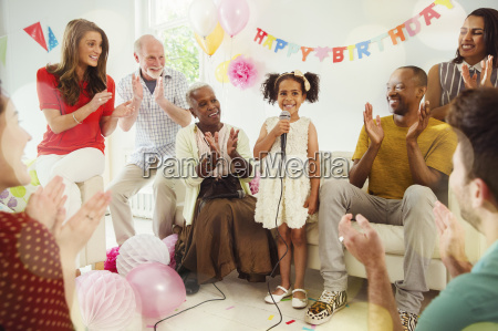 multi ethnic family clapping for girl