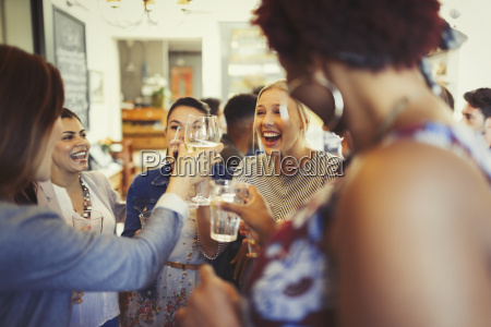 enthusiastic women friends toasting wine glasses
